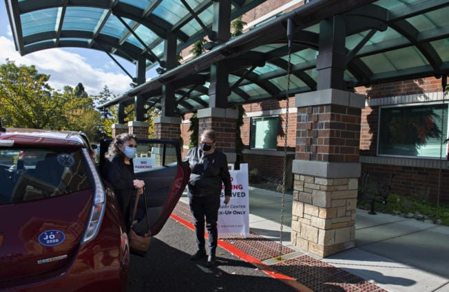 Bennye Wright of Vancouver exits the car with the help of Connie Pickering of the Human Services Council as she arrives for her appointment at The Vancouver Clinic on Wednesday afternoon. Both demand for rides and the number of volunteer drivers have been reduced during the pandemic.
