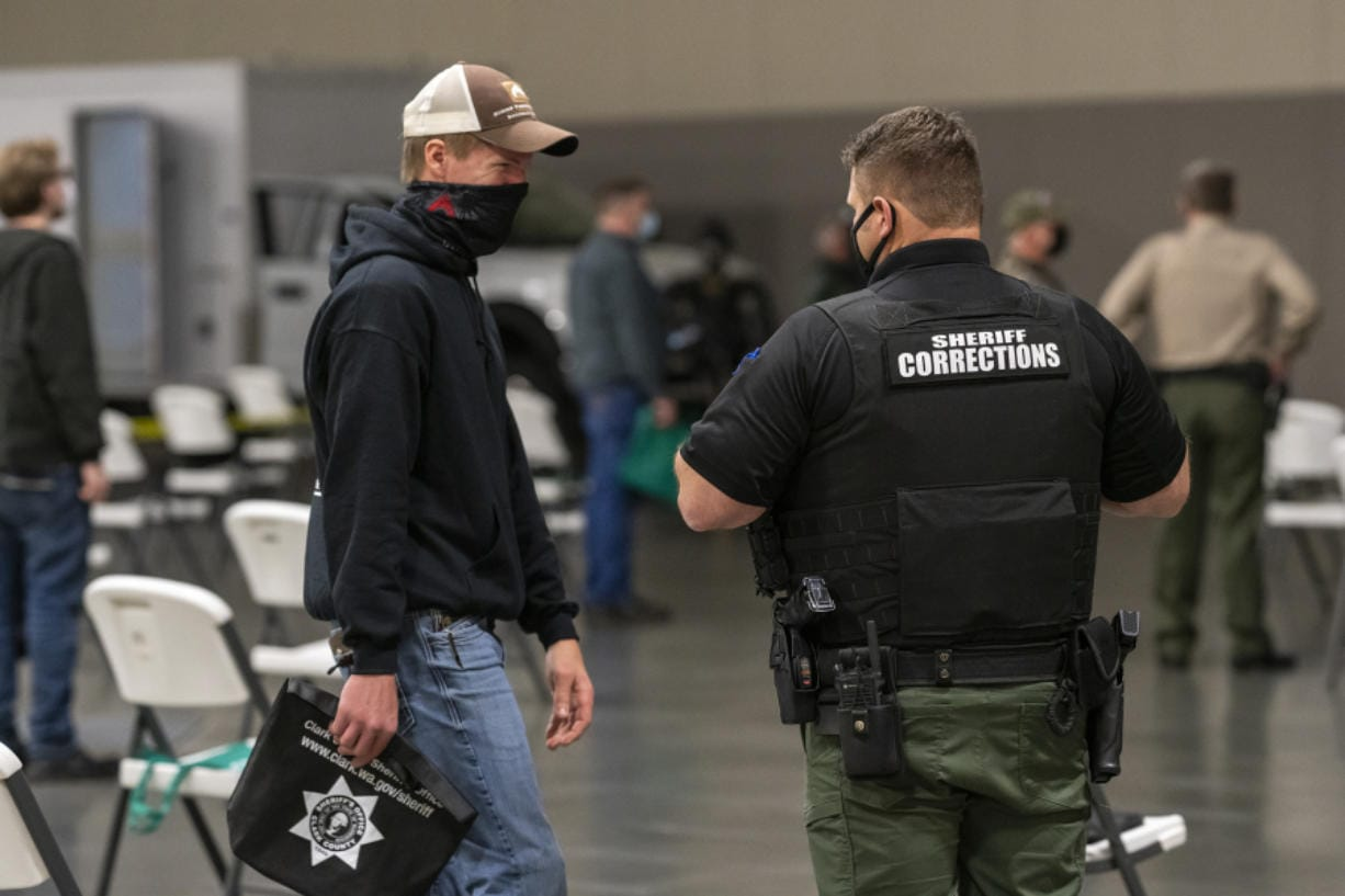 Zach Nygaard, left, speaks with a deputy in a socially distanced seating area during a recruitment event for Clark County Jail corrections deputies Tuesday evening at the Clark County Event Center at the Fairgrounds.