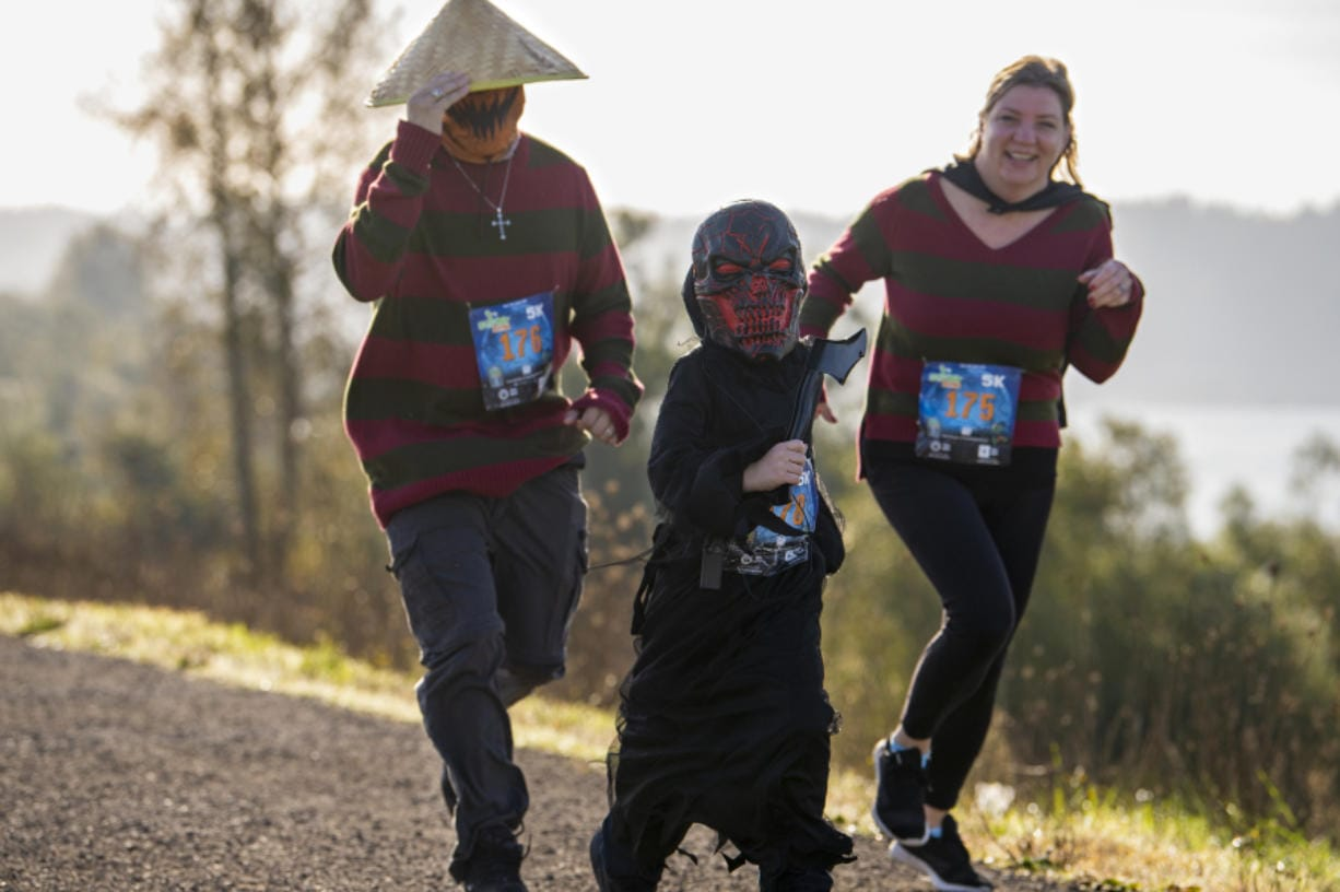 Joey Catania, from left, runs alongside 7-year-old Maxx Catania and Crystal Catania in WhyRacingis Scary Run on Saturday morning, October 31, 2020, in Washougal. Roughly 300 runners, many costumed, enjoyed a sunny morning along the Columbia River taking part in the family-friendly event, which featured 5- and 10-kilometer courses and a half marathon.