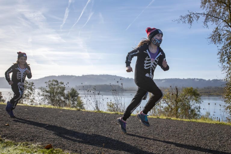 Eight-year-old Sophia Campbell, left, runs behind Emily Corsen, 10, in WhyRacing's Scary Run on Saturday morning, October 31, 2020, in Washougal. (Joshua Hart/The Columbian)