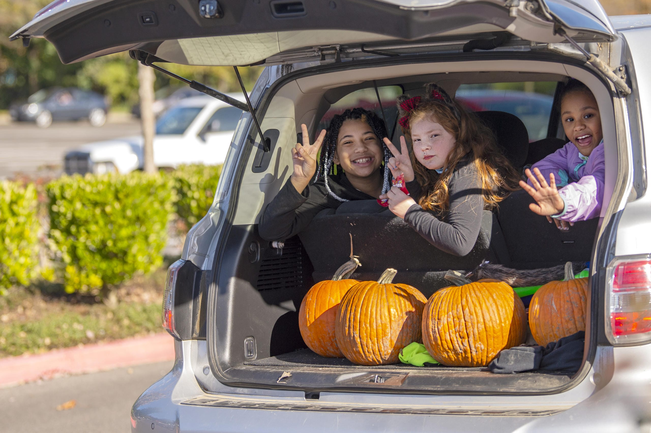 Kaia Silva, 11, from left, Juliann Galey, 9, and Leilani Quint, 9, smile and wave at the camera while looking out the back of an SUV as part of fourth annual Booville, a drive-through Halloween event put on by the Parks Foundation of Clark County at Vancouver Mall on Saturday. (Joshua Hart/The Columbian