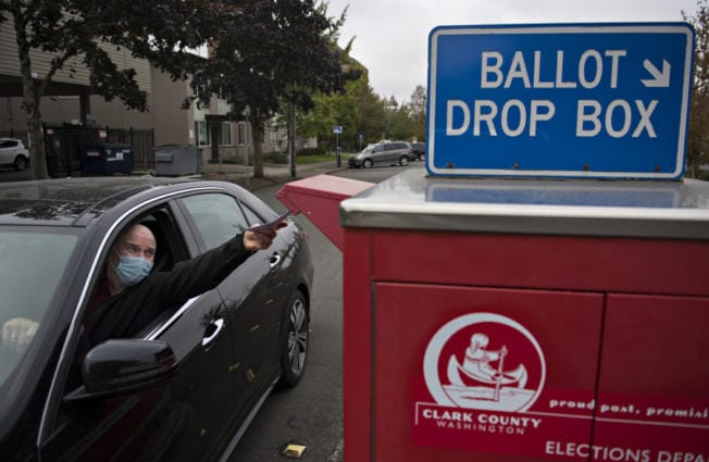 Ridgefield resident Anthony Bilic wears a protective mask as he gets his vote in early at a downtown Vancouver ballot drop box Thursday afternoon. Bilic was among a steady stream of voters who came out on Thursday in advance of next week's election.