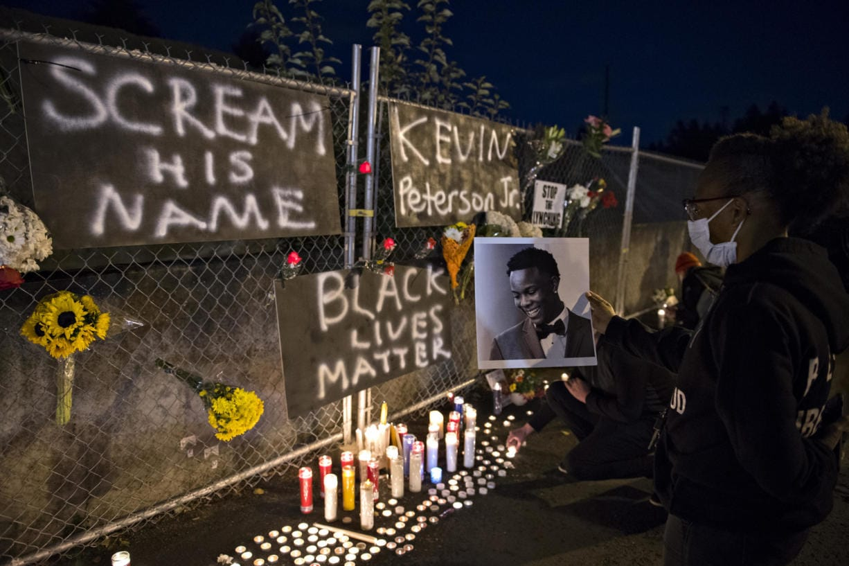 Alisha, one of the event organizers who declined to give her last name, holds a photo of Kevin Peterson Jr., a 21-year-old Black Camas man who was killed Thursday, as he is remembered with a candlelight vigil at the Hazel Dell branch of U.S. Bank on Friday night, Oct. 30, 2020.