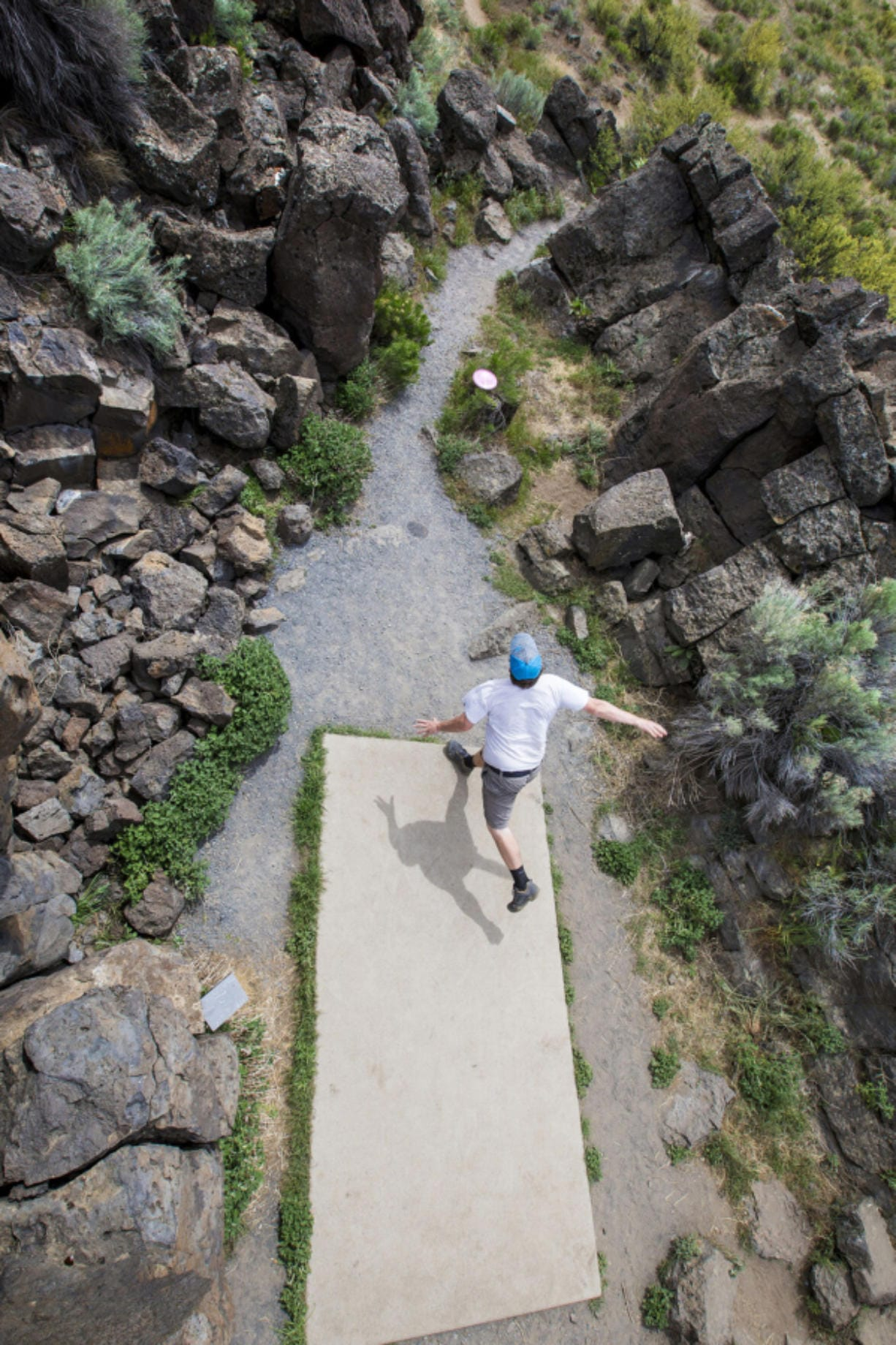 Nate Anderson of Bend throws his disk through a tight rock outcropping at the seventh hole tee box during a round of disk golf at Pine Nursery Park this summer.