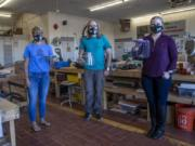 Irm Diorio (left), director of Decatur Makers, William Strika (center), executive director of Roswell Firelabs and Skyler Holobach (right), co-founder of Atlanta Shield Makers, pose with face shields they created on Tuesday, Oct. 6, 2020 at Roswell Firelabs in Roswell, Georgia.