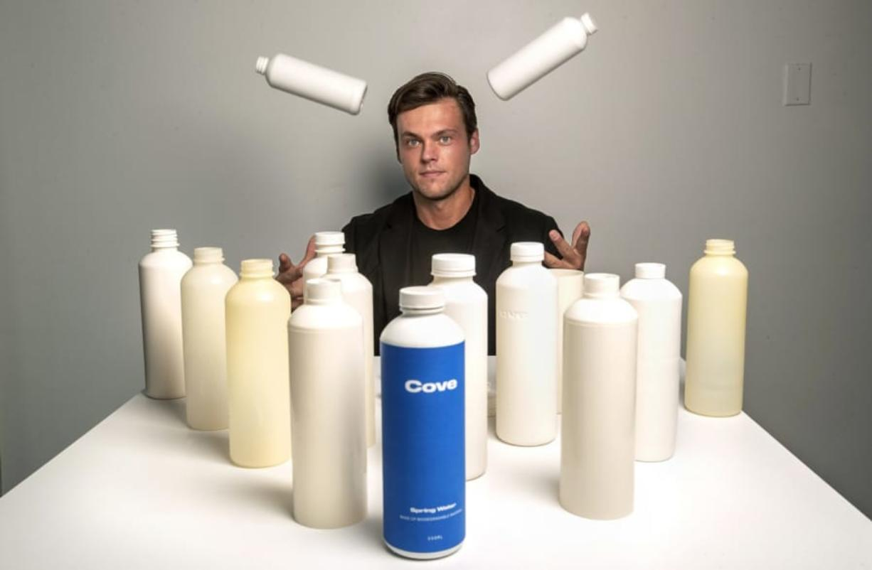Alex Totterman, CEO and founder of Cove Water in Culver City, Calif., is photographed on Oct. 2, 2020 with a mix of prototype and actual plastic water bottles, as well as bottle caps and label that he says are made up entirely of biodegradable material. The company will begin selling the bottled water sometime in the fall.