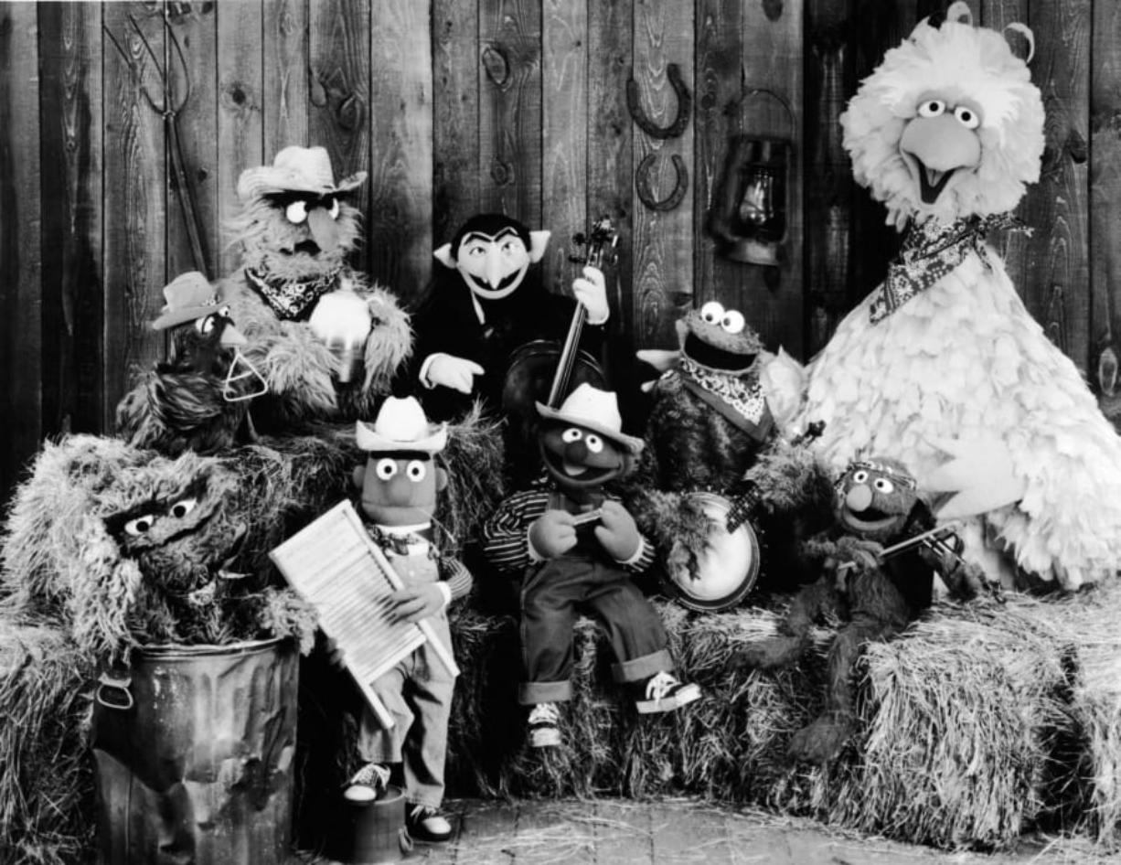 Publicity still of the Sesame Street Muppets taken to promote their record album, 'Sesame Country,' July 1, 1981. Included are Oscar the Crouch (in garbage can), Bert (holding washboard), Ernie (harmonica), the Count (bass), Cookie Monster (banjo), Grover (violin), and Big Bird (far right).