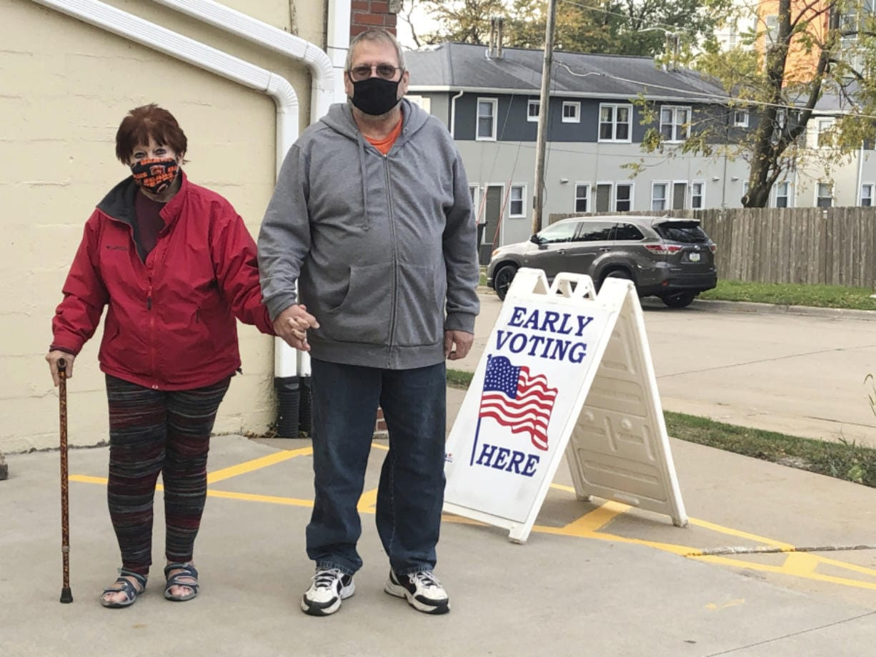 Tim and Pat Tompkins pause for a picture on their way to early vote in Bettendorf, Iowa, Friday, Oct. 16, 2020. Tompkins said he and his wife, Pat, were concerned about coronavirus exposure in bigger crowds and brought their own sanitizer, but were determined to vote.
