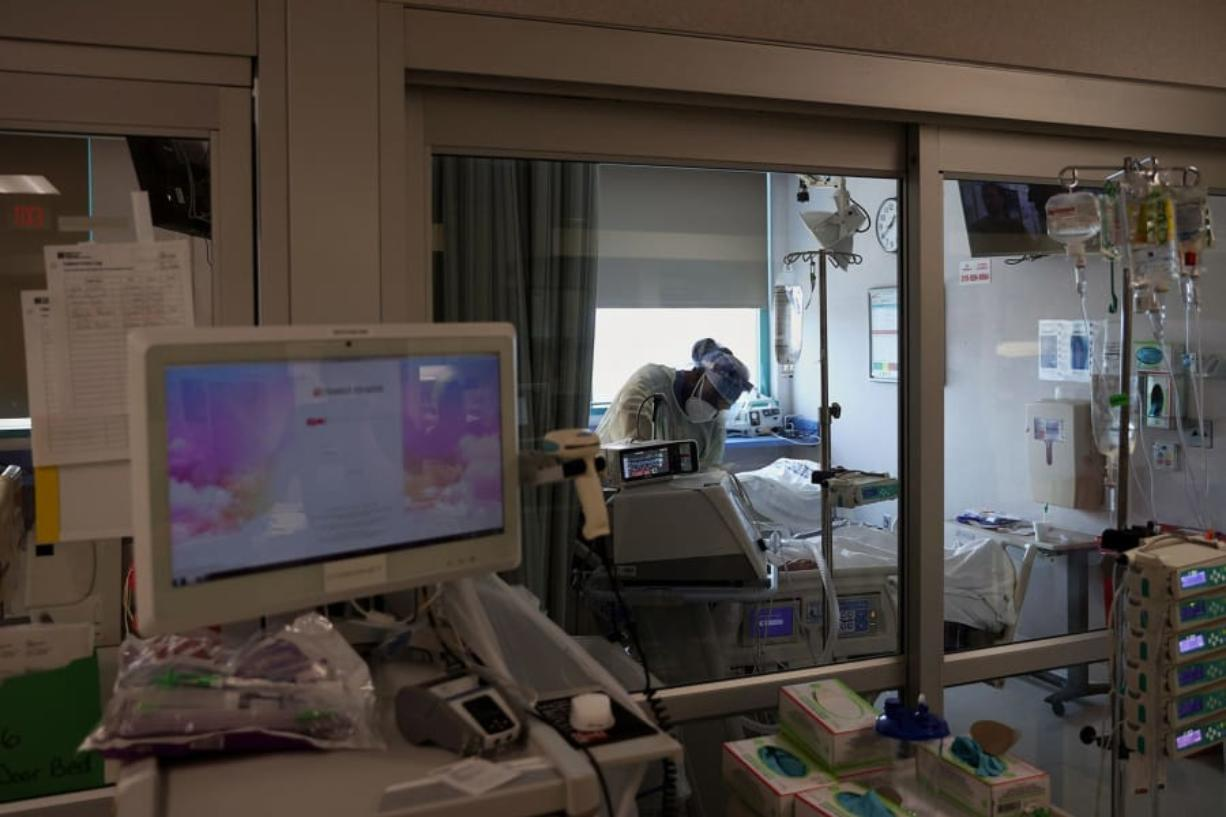 A medical worker works inside a patient room in a COVID-19 intensive care unit at Temple University Hospital's Boyer Pavilion in North Philadelphia on Tuesday, April 7, 2020.
