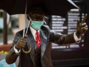 """The """"Umbrella Man"""" statue in downtown Portland's Pioneer Square wears a face mask in April."""