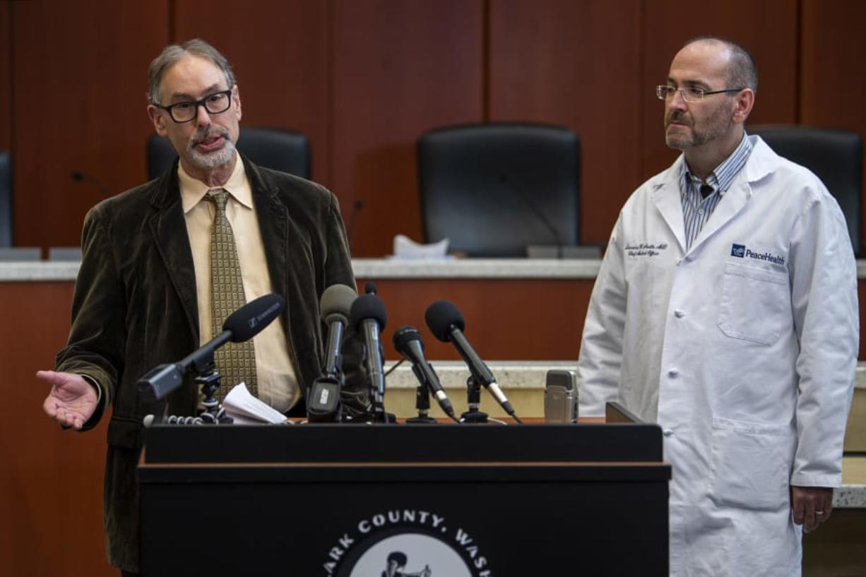 Clark County Public Health Officer Dr. Alan Melnick, left, and Dr. Lawrence Neville, chief medical officer at PeaceHealth Southwest, speak March 13 during a COVID-19 press conference at the Clark County Public Service Center. Seven months later, the pandemic is no closer to being over.