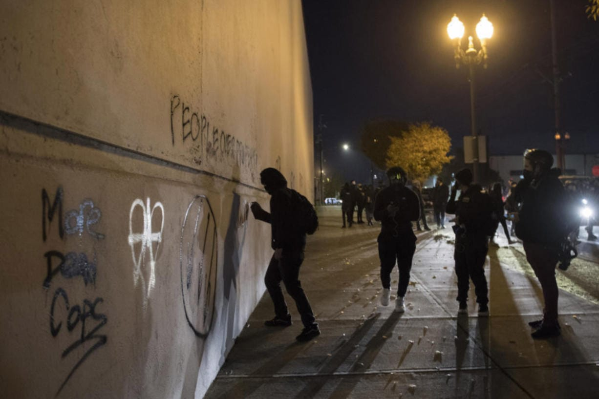 Protesters tag a wall with spray paint in downtown Vancouver on Friday night. Some windows also were smashed.