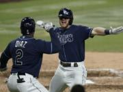 Tampa Bay Rays' Michael Brosseau, right, celebrates with Yandy Diaz after hitting a solo home run during the eighth inning in Game 5 of a baseball American League Division Series against the New York Yankees, Friday, Oct. 9, 2020, in San Diego. (AP Photo/Jae C.