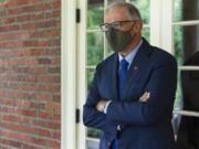 Washington Gov. Jay Inslee pauses on a walkway outside the Governor's Mansion after taking part in an AP interview, Friday, Sept. 25, 2020, in Olympia. (AP Photo/Ted S.