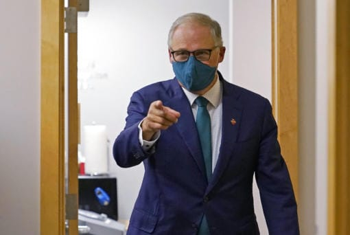 Washington Gov. Jay Inslee, a Democrat, points to a member of his team after taking part in a debate with Loren Culp, a Republican, Wednesday, Oct. 7, 2020, in Olympia, Wash. Due to concerns over COVID-19, each candidate took part in the debate from an individual room, separate from moderators. (AP Photo/Ted S.