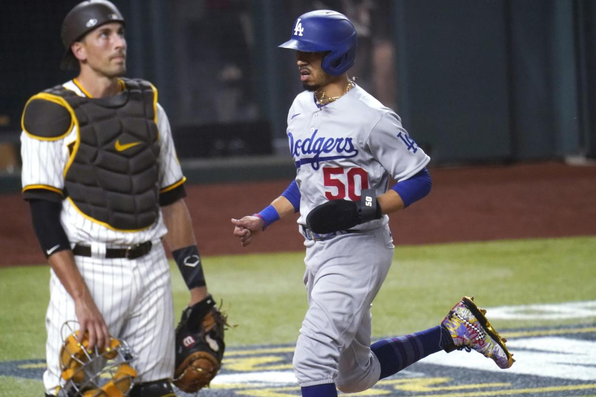 Los Angeles Dodgers' Mookie Betts (50) scores on a throwing error by San Diego Padres' Fernando Tatis Jr. during the third inning in Game 3 of a baseball National League Division Series Thursday, Oct. 8, 2020, in Arlington, Texas. At left is San Diego Padres catcher Jason Castro.