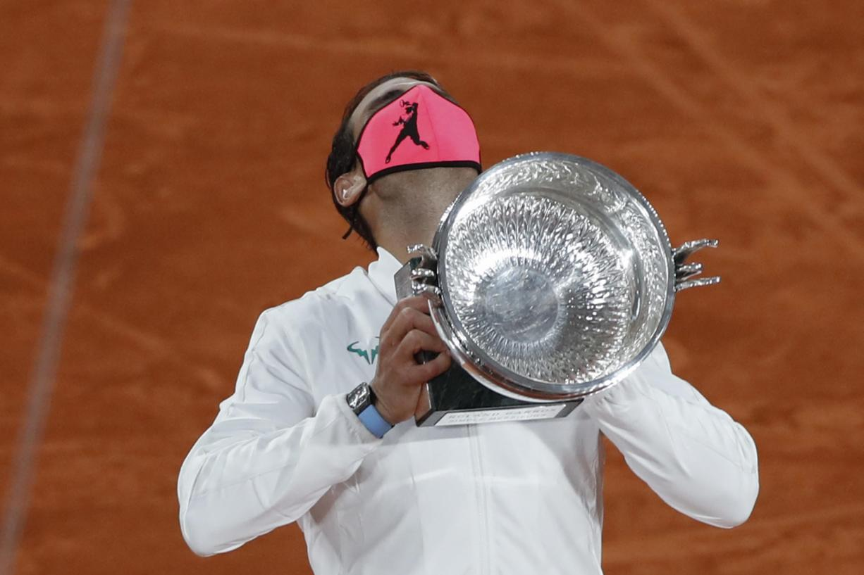 Spain's Rafael Nadal holds the trophy as he celebrates winning the final match of the French Open tennis tournament against Serbia's Novak Djokovic in three sets, 6-0, 6-2, 7-5, at the Roland Garros stadium in Paris, France, Sunday, Oct. 11, 2020.
