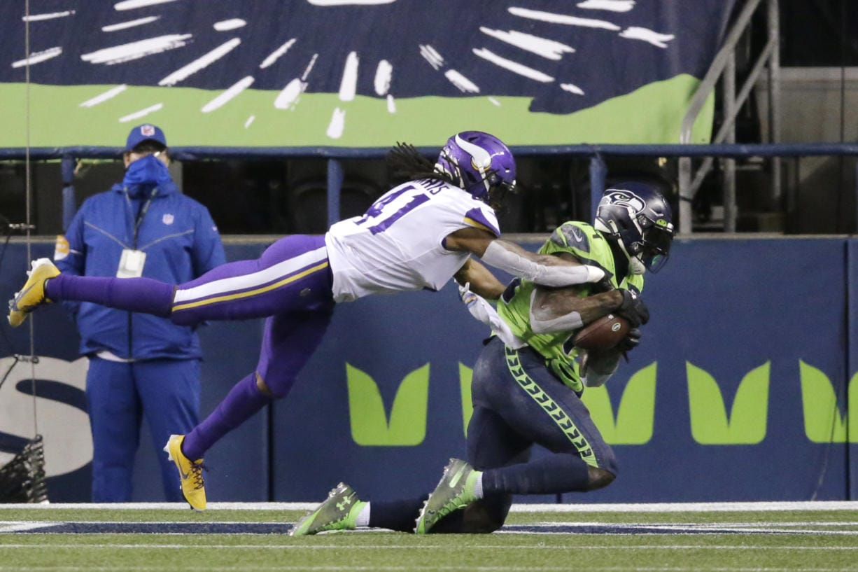 Seattle Seahawks' DK Metcalf, right, catches the ball in the end zone for a touchdown as Minnesota Vikings' Anthony Harris defends near the end of the second half of an NFL football game, Sunday, Oct. 11, 2020, in Seattle.