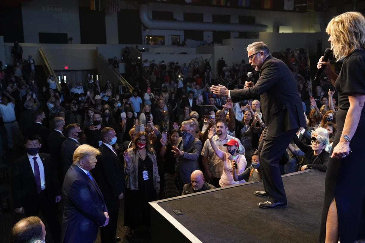 President Donald Trump, lower left, attends church at International Church of Las Vegas, as Pastor Pasqual Urrabazo, second from the right, gestures on stage, Sunday, Oct. 18, 2020, in Las Vegas, Nev.
