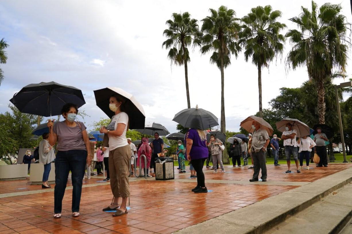 People wait in line in the rain outside of an early voting site, Monday, Oct. 19, 2020, in Miami. Florida begins in-person early voting in much of the state Monday. With its 29 electoral votes, Florida is crucial to both candidates in order to win the White House.