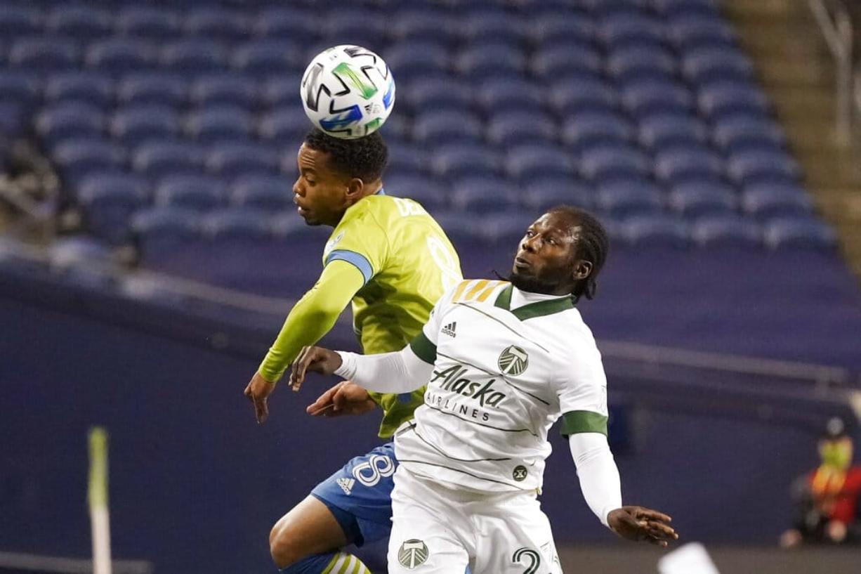Seattle Sounders' Jordy Delem (8) heads the ball in front of Portland Timbers' Yimmi Chara in the first half of an MLS soccer match, Thursday, Oct. 22, 2020, in Seattle.
