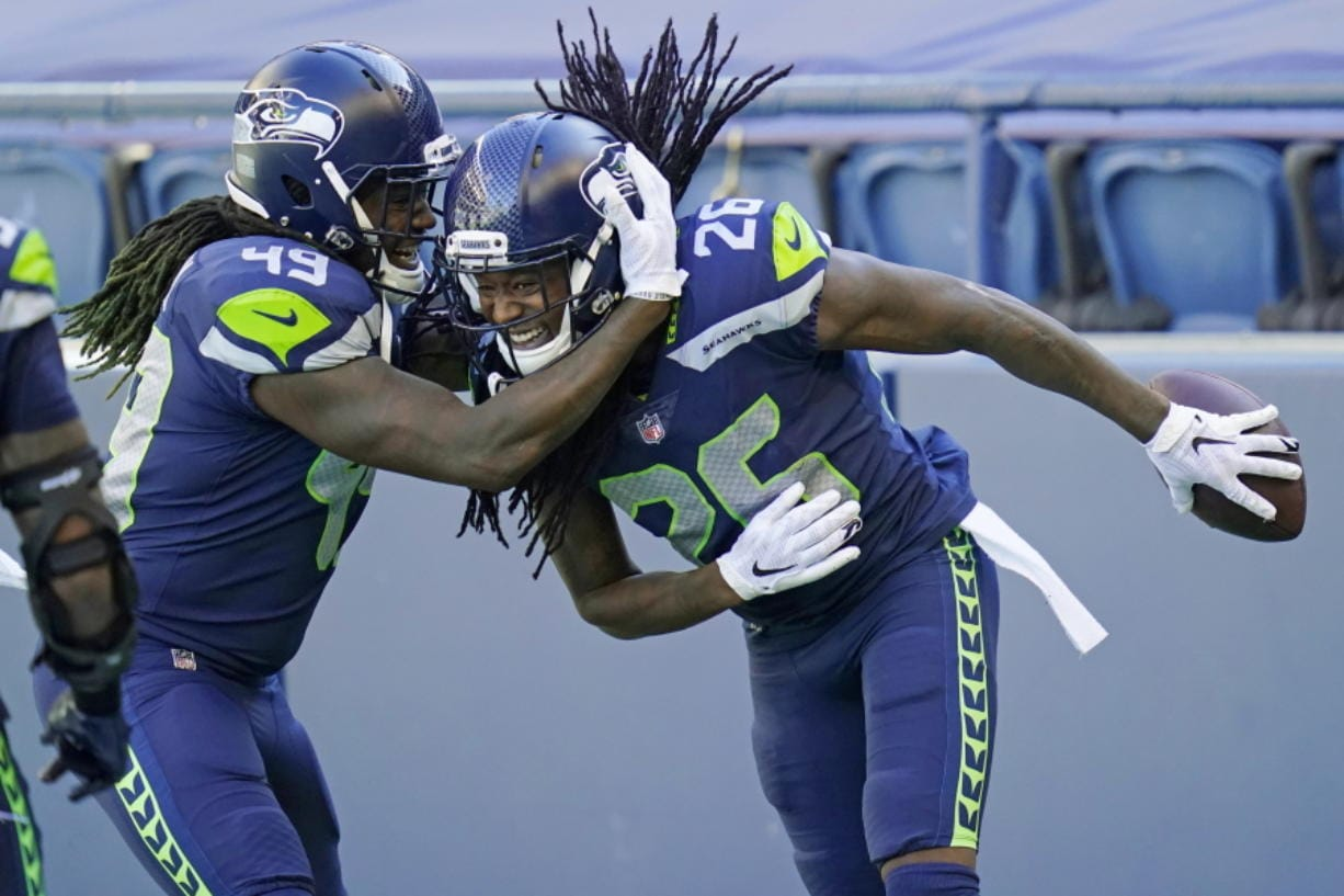 Seattle Seahawks cornerback Shaquill Griffin (26) is greeted by his twin brother, outside linebacker Shaquem Griffin (49), after Shaquill Griffin intercepted a pass against the Dallas Cowboys during the first half of an NFL football game, Sunday, Sept. 27, 2020, in Seattle.
