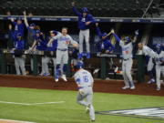 The Los Angeles Dodgers celebrate a three-run home run by Will Smith against the Atlanta Braves during the sixth inning in Game 5 of a baseball National League Championship Series Friday, Oct.