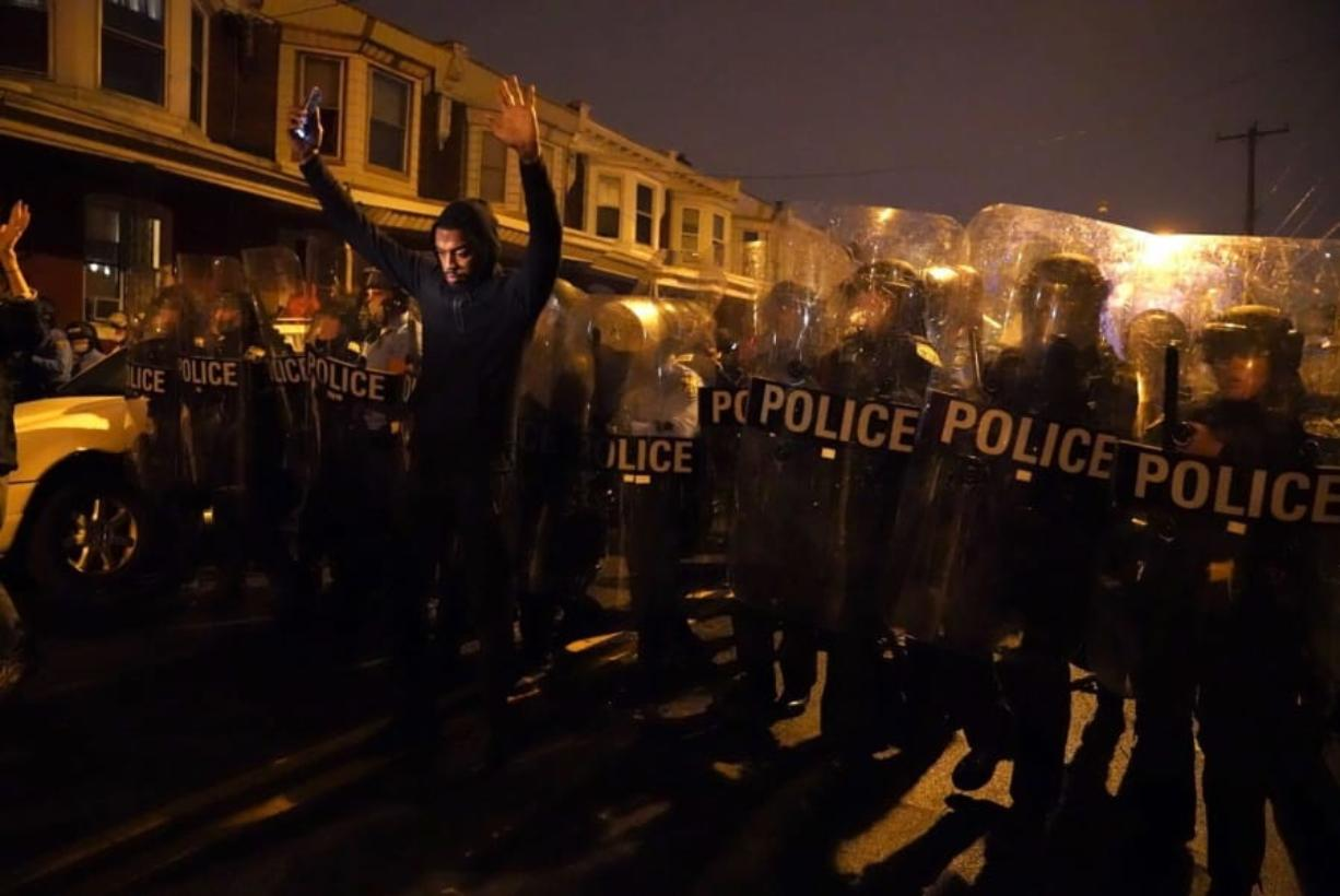 Sharif Proctor lifts his hands up in front of the police line during a protest in response to the police shooting of Walter Wallace Jr., Monday, Oct. 26, 2020, in Philadelphia. Police officers fatally shot the 27-year-old Black man during a confrontation Monday afternoon in West Philadelphia that quickly raised tensions in the neighborhood.