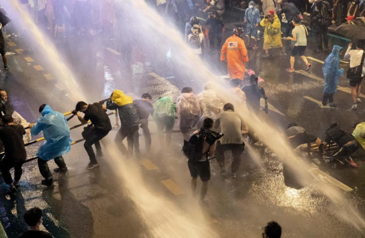 Pro democracy demonstrators face water canons as police try to disperse them from their protest venue in Bangkok, Thailand, Friday, Oct. 16, 2020. Thailand prime minister has rejected calls for his resignation as his government steps up efforts to stop student-led protesters from rallying in the capital for a second day in defiance of a strict state of emergency.