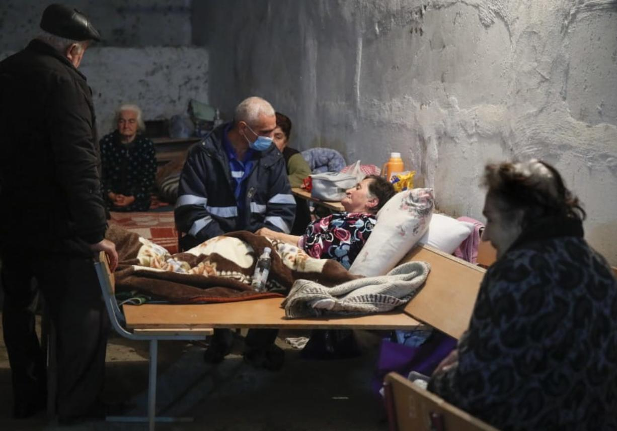 A medical worker talks to a sick woman in a bomb shelter in Stepanakert, the separatist region of Nagorno-Karabakh, Thursday, Oct. 22, 2020. Heavy fighting over Nagorno-Karabakh continued Thursday with Armenia and Azerbaijan trading blame for new attacks, hostilities that raised the threat of Turkey and Russia being drawn into the conflict.