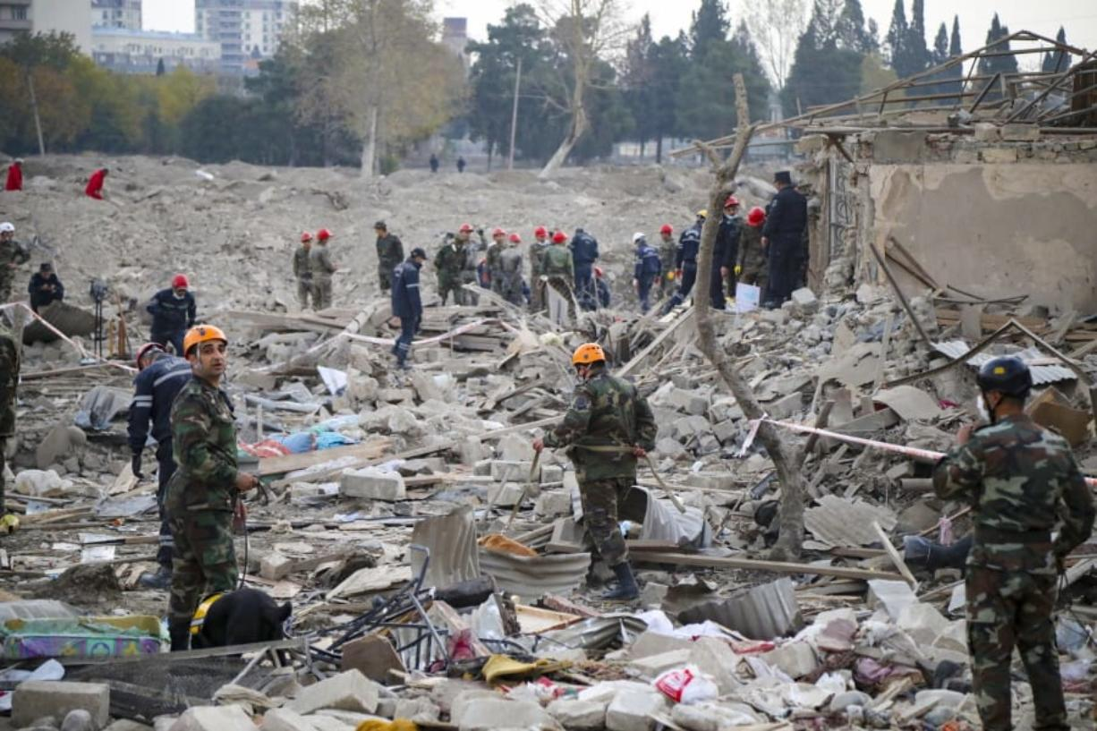 Soldiers and firefighters search for survivors in a residential area that was hit by rocket fire overnight by Armenian forces, early Saturday, Oct. 17, 2020, in Gyanga, Azerbaijan's second largest city, near the border with Armenia.