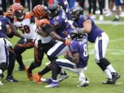 Cincinnati Bengals defensive end Carlos Dunlap (96) is able to sack Baltimore Ravens quarterback Lamar Jackson (8) in spite of being blocked by Ravens offensive tackle Orlando Brown (78) during the first half of an NFL football game, Sunday, Oct. 11, 2020, in Baltimore.