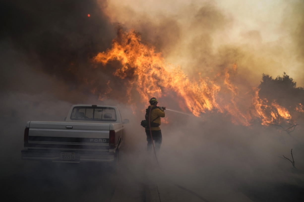 Firefighter Raymond Vasquez battles the Silverado Fire Monday, Oct. 26, 2020, in Irvine, Calif. A fast-moving wildfire forced evacuation orders for 60,000 people in Southern California on Monday as powerful winds across the state prompted power to be cut to hundreds of thousands to prevent utility equipment from sparking new blazes. (AP Photo/Jae C.