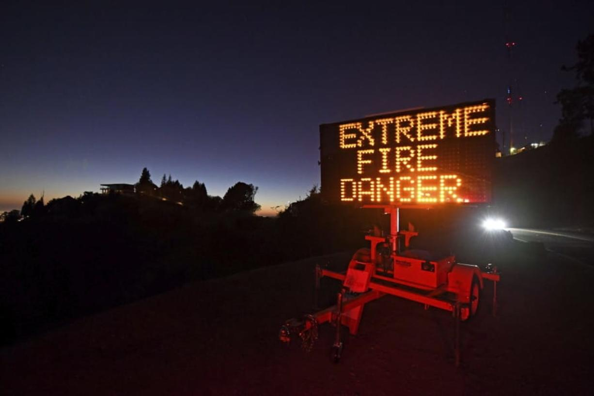 A roadside sign warns motorists of extreme fire danger on Grizzly Peak Boulevard, in Oakland, Calif., Sunday, Oct. 25, 2020. Due to high winds and dry conditions PG&E will turn off the power to over 361,000 customers in 36 counties to protect them from possible wildfires caused by downed power lines. The National Weather Service predicts offshore winds from the north peaking at higher elevations up to 70 mph.