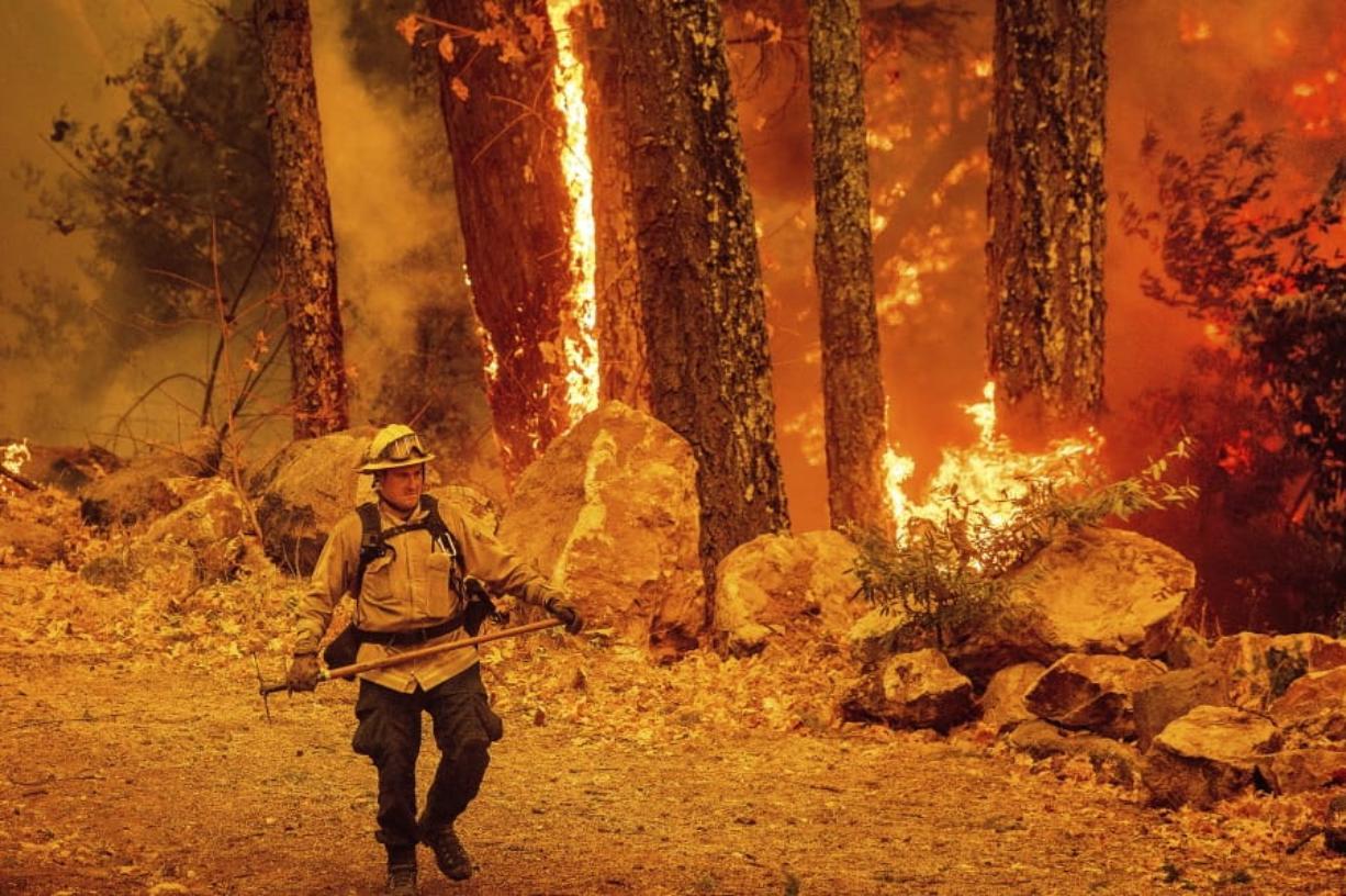 A firefighter walks along a path as the Glass Fire burns Thursday along Highway 29 in Calistoga, Calif.