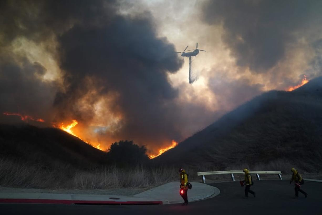 A helicopter drops water as firefighters walk with drip torches to set a backfire against the Blue Ridge Fire on Tuesday, Oct. 27, 2020, in Chino Hills, Calif. Facing extreme wildfire conditions this week that included hurricane-level winds, the main utility in Northern California cut power to nearly 1 million people while its counterpart in Southern California pulled the plug on just 30 customers to prevent power lines and other electrical equipment from sparking a blaze. (AP Photo/Jae C.