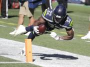Seattle Seahawks running back Chris Carson (32) dives near the end zone during the first half of an NFL football game against the Dallas Cowboys, Sunday, Sept. 27, 2020, in Seattle. The Seahawks won 38-31.