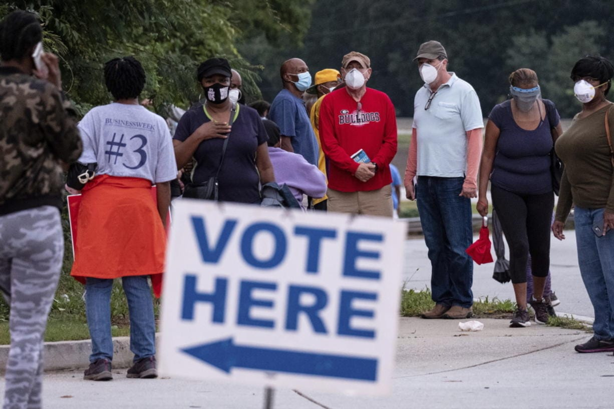 People wait in line to vote in Decatur, Ga., Monday, Oct. 12, 2020.