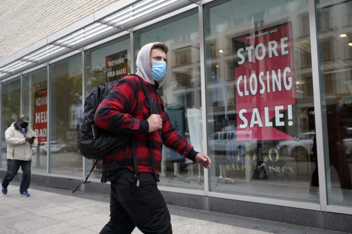 A passer-by walks past a store closing sign, right, in the window of a department store, Tuesday, Oct. 27, 2020, in Boston.  Americans may feel whiplashed by a report Thursday, Oct. 29,  on the economy's growth this summer, when an explosive rebound followed an epic collapse.