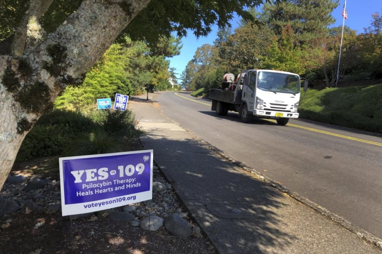 A truck drives past a sign supporting a ballot measure that would legalize controlled, therapeutic use of psilocybin mushrooms, Friday, Oct. 9, 2020 in Salem, Ore. War veterans with PTSD, terminally ill patients and others suffering from anxiety are backing the ballot measure.
