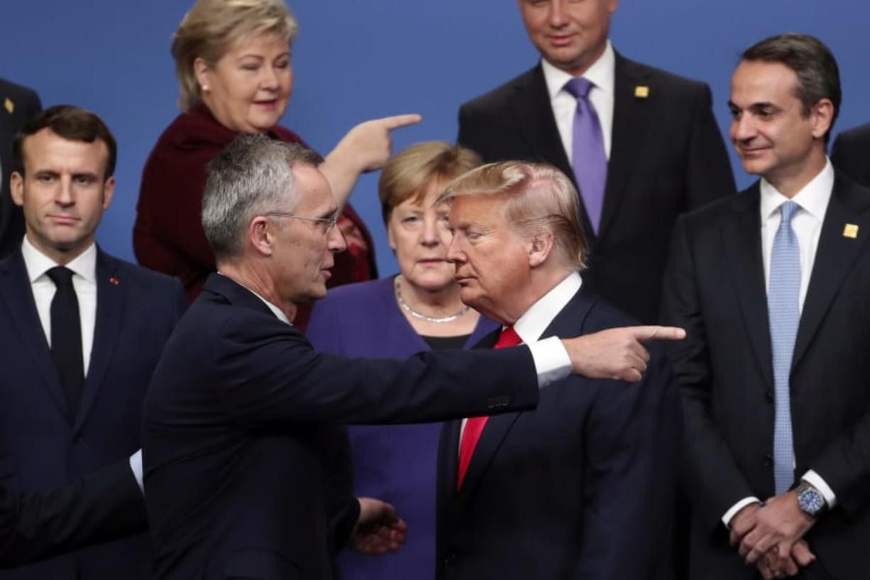 FILE - In this Dec. 4, 2019, file photo, NATO Secretary General Jens Stoltenberg, front left, speaks with U.S. President Donald Trump, front right, after a group photo at a NATO leaders meeting at The Grove hotel and resort in Watford, Hertfordshire, England. There will be leaders and populations who shudder at the thought of four more years of the Donald Trump administration and those whose consternation is tied to his potential defeat, and a U.S. government led by a President Joe Biden.