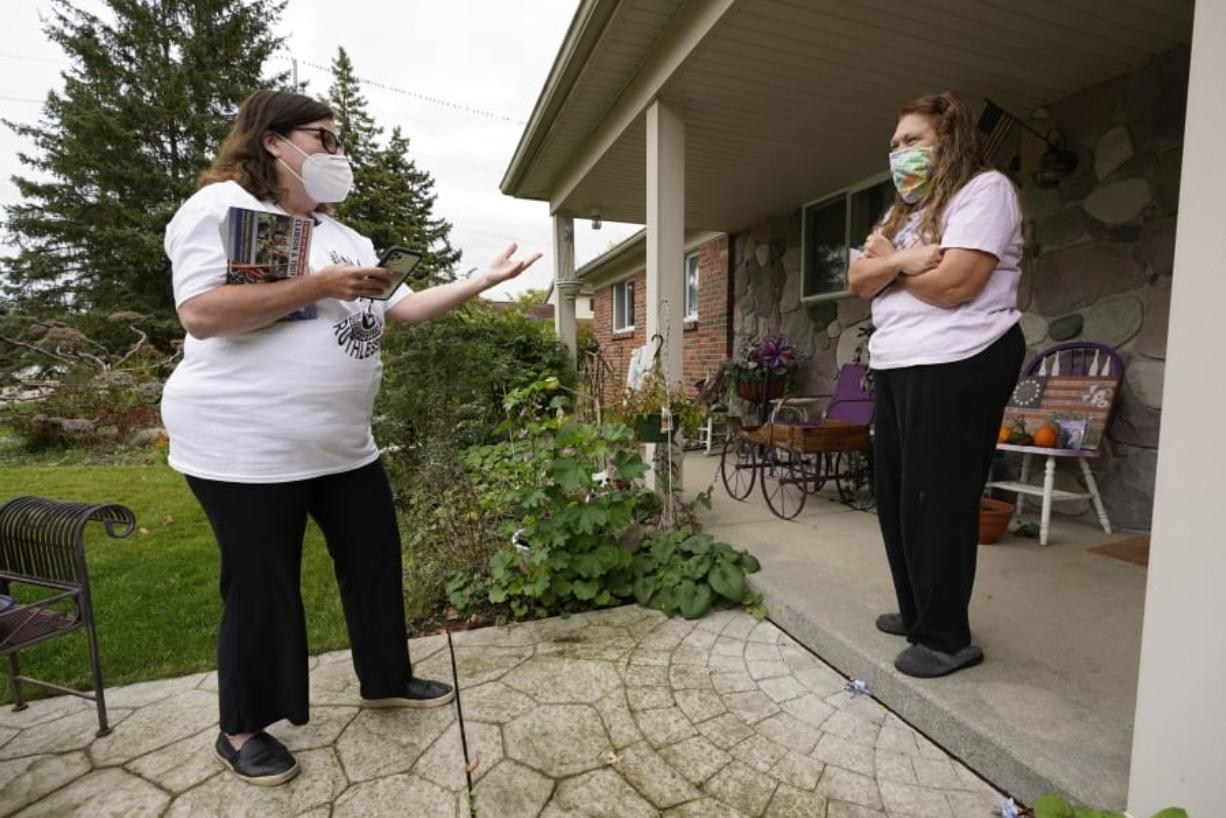 Lori Goldman, talks with a voter while canvassing in Troy, Mich., Thursday, Oct. 15, 2020. Goldman spends every day door knocking for Democrats in Oakland County, an affluent Detroit suburb. She feels responsible for the country's future: Trump won Michigan in 2016 by 10,700 votes and that helped usher him into the White House. Goldman believes people like her -- suburban white women -- could deliver the country from another four years of chaos.