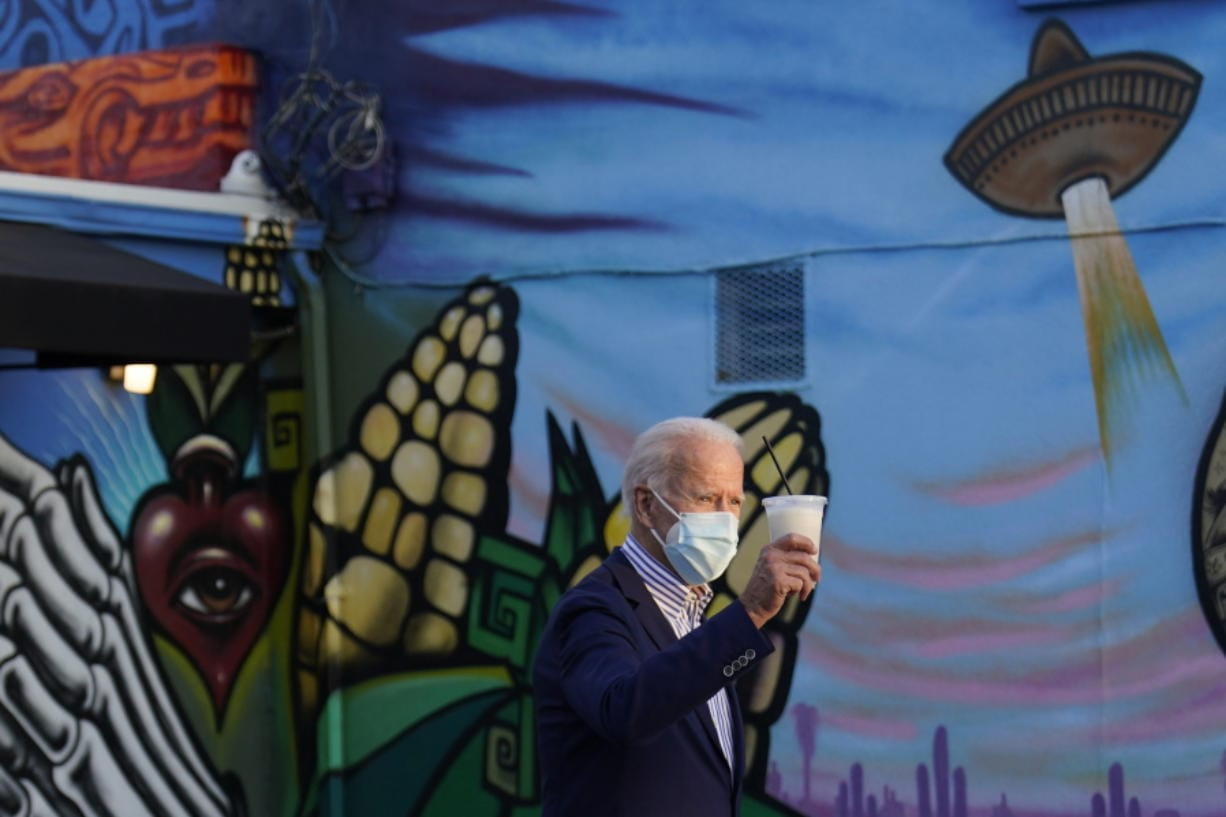 Democratic presidential candidate former Vice President Joe Biden holds a beverage as he leaves Barrio Cafe in Phoenix, Thursday, Oct. 8, 2020, during their small business bus tour.