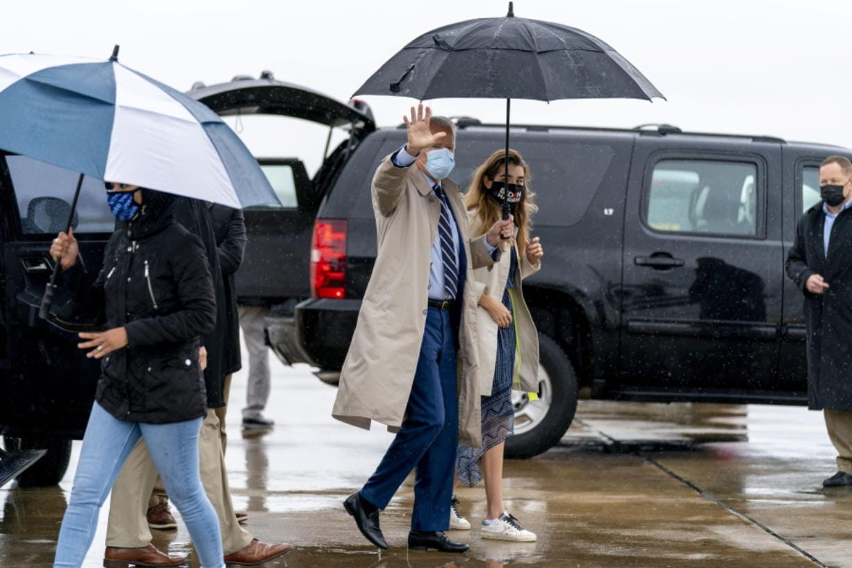 Democratic presidential candidate former Vice President Joe Biden, accompanied by his granddaughter Natalie Biden, right, boards his campaign plane at New Castle Airport in New Castle, Del., Thursday, Oct. 29, 2020, to travel to Florida for drive-in rallies.