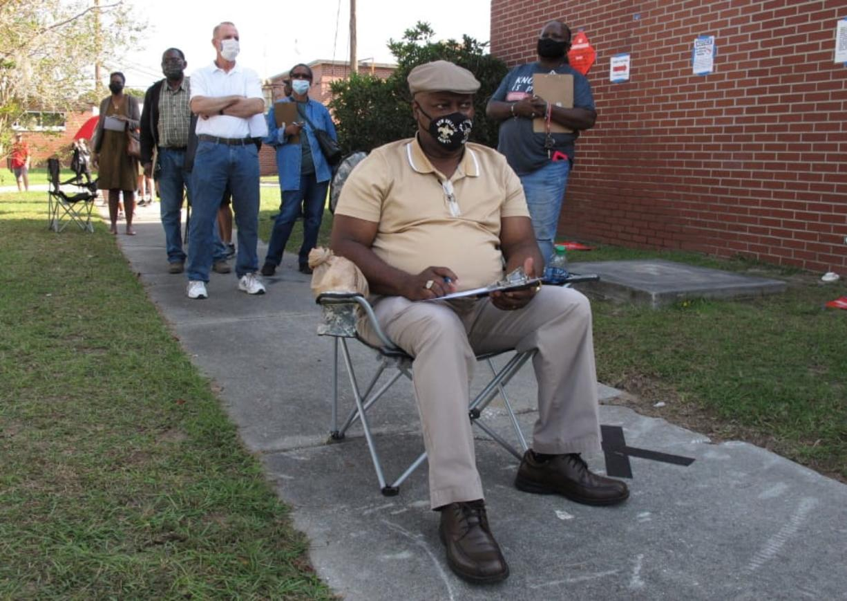 Richard Williams sits in a folding chair, filling out paperwork, as he waits in line to vote early in Savannah, Ga., on Wednesday, Oct. 14, 2020. Black people are going to the polls by the thousands and waiting in lines for hours to vote early in Georgia.