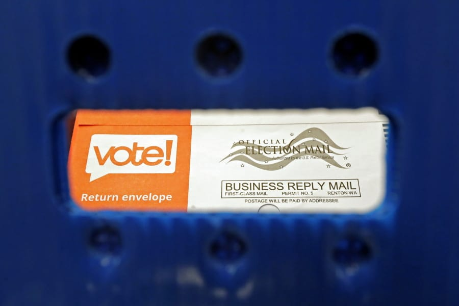 FILE - In this Aug. 5, 2020, file photo a vote-by-mail ballot is shown as viewed through the handle of a sorting tray at the King County Elections headquarters in Renton, Wash., south of Seattle. U.S. Postal Service records show delivery delays have persisted across the country as millions of Americans began voting by mail, raising the possibility of ballots being rejected because they arrive too late. Postal data covering the beginning of October show nearly all of the agency's delivery regions missing agency targets of having more than having more than 95% of first-class mail arrive within five days. (AP Photo/Ted S.