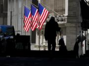 FILE - In this Oct. 14, 2020 file photo, pedestrians pass the New York Stock Exchange in New York. Stocks are opening higher on Wall Street Tuesday, Oct. 20 as traders look over several solid earnings reports from U.S. companies.
