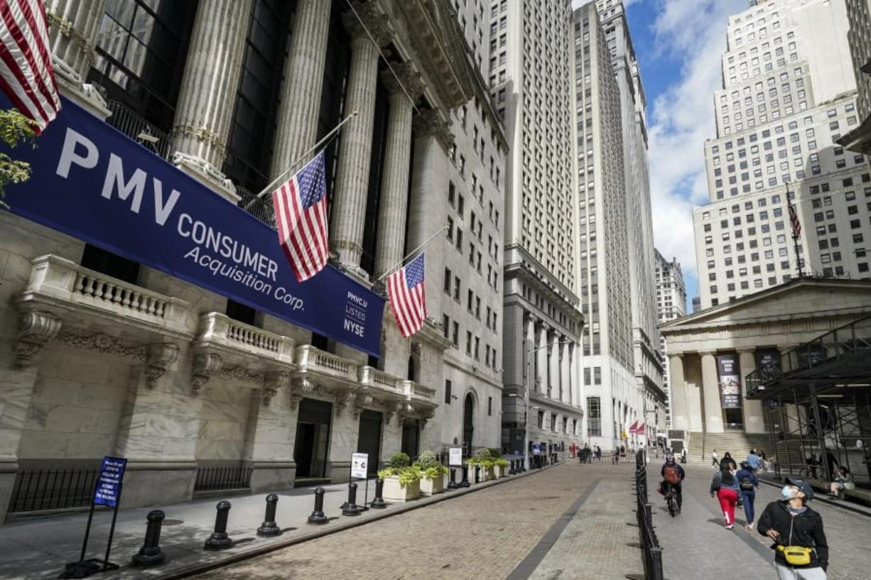 FILE - Pedestrians pass the New York Stock Exchange, Friday, Oct. 2, 2020, in New York.   U.S. stocks are drifting on Thursday, Oct. 22,  as more big companies report profits for the summer that were better than Wall Street feared.