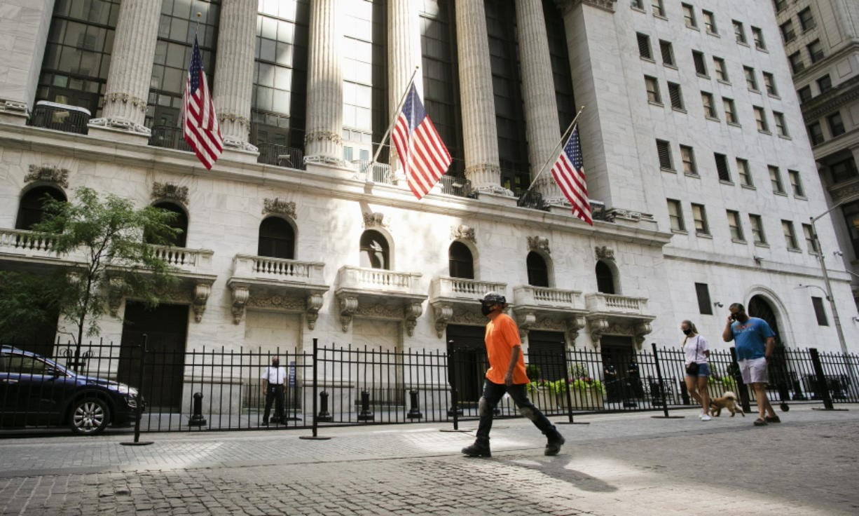 FILE- In this July 21, 2020 file photo, people walk by the New York Stock Exchange.  Stocks are falling in early trading on Friday, Oct. 30,  as Wall Street closes out a punishing week and its first back-to-back monthly loss since March, when worries about the pandemic were first peaking.