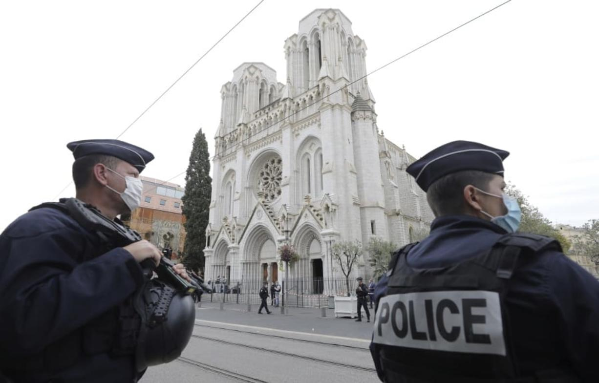 Police officers stand guard near Notre Dame church in Nice, southern France, Thursday, Oct. 29, 2020. An attacker armed with a knife killed at least three people at a church in the Mediterranean city of Nice, prompting the prime minister to announce that France was raising its security alert status to the highest level. It was the third attack in two months in France amid a growing furor in the Muslim world over caricatures of the Prophet Muhammad that were re-published by the satirical newspaper Charlie Hebdo.